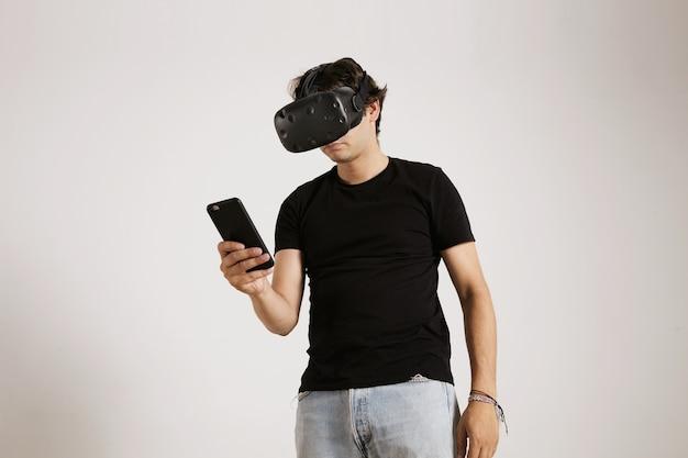Ein spieler in vr-brille und schlichtem schwarzem t-shirt, der sein smartphone lokalisiert auf weiß betrachtet