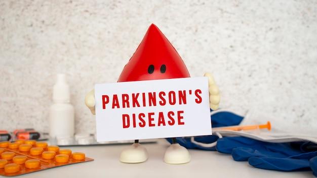 Ein spielzeugbluttropfen enthält eine weiße papierkarte mit der aufschrift parkinsons disease. medizinisches konzept.