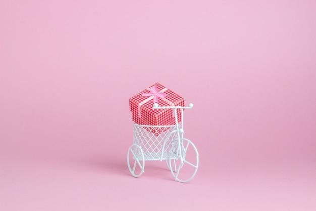 Ein spielzeugfahrrad trägt ein geschenk. die idee für eine postkarte.