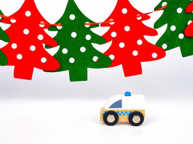 Ein spielzeugkrankenwagen vor rotem und grünem kiefernhintergrund