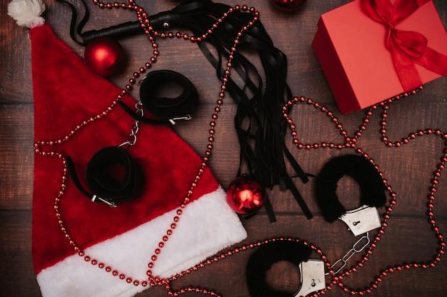 Ein spielzeugset für erwachsene mit weihnachtsdekor. flatley. ein beispiel für ein geschenk. handschellen, peitsche, analplug, weihnachtskugeln.