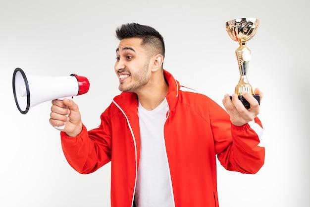 Ein sportler in einer sportroten uniform gibt den gewinner bekannt und hält einen goldenen pokal auf weißem grund.