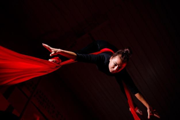 Ein sportmädchen führt gymnastik- und zirkusübungen auf roter seide durch. studioaufnahmen auf dunklem hintergrund. luftgymnastik auf leinwand