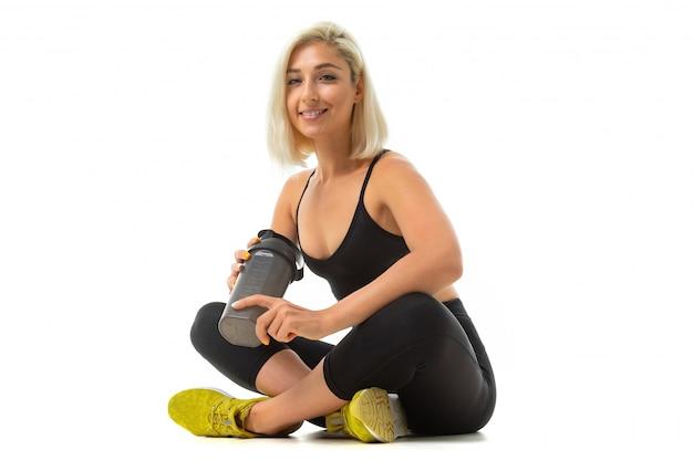 Ein sportmädchen mit blonden haaren und heller maniküre in kopfhörern, schwarzen sportthemen, leggings und gelbem sneaker hält eine sportwasserflasche.