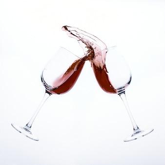 Ein spritzer rotwein aus zwei glasgläsern isoliert auf einer weißen oberfläche