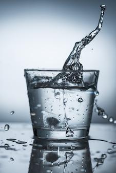 Ein spritzer wasser in einem transparenten glas auf einer spiegelfläche.