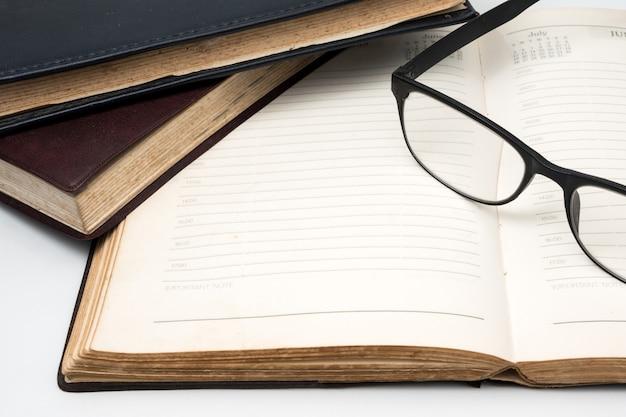 Ein stapel alte bücher mit notizbuch und brillen auf einem weißen hintergrund.