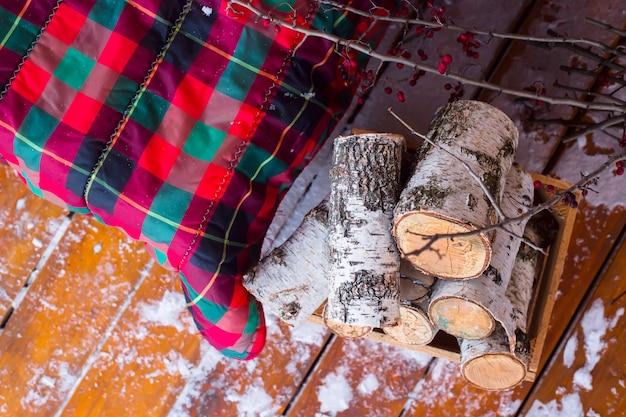 Ein stapel birkenholz nahe dem sofa mit einer roten karierten wolldecke auf der schneebedeckten terrasse des offenen winters