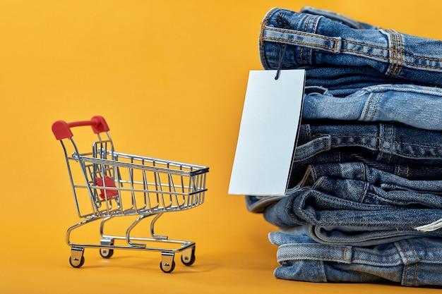 Ein stapel blue jeans mit einem weißen leeren etikett auf einem gelben hintergrund