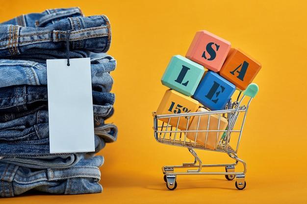 Ein stapel blue jeans mit einem weißen leeren tag auf gelbem grund. einkaufswagen mit bunten würfeln. verkaufswort geschrieben auf würfel. verkaufskonzept. haufen stylischer trendiger jeanshosen.
