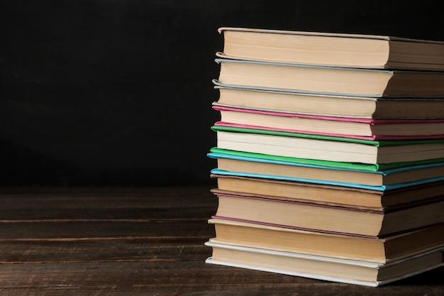 Ein stapel bücher auf einem braunen holztisch und auf schwarzem hintergrund. alte bücher. ausbildung. schule. arbeitszimmer mit platz für inschriften