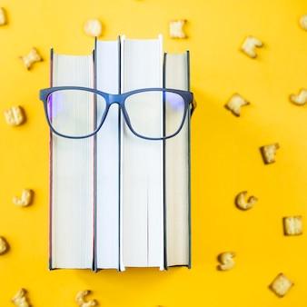 Ein stapel bücher mit brille ist das bild eines gesichts einer person