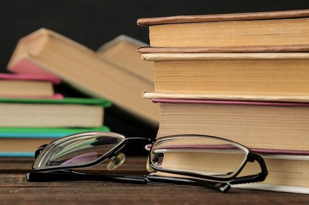 Ein stapel bücher und gläser auf einem braunen holztisch und auf schwarzem hintergrund. alte bücher. ausbildung. schule. lernen