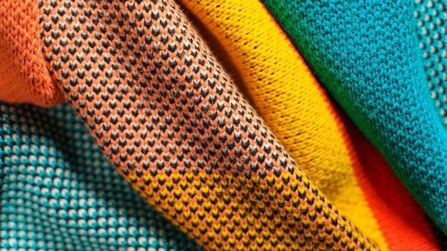 Ein stapel bunter strickwaren mit unterschiedlichen strukturen und texturen