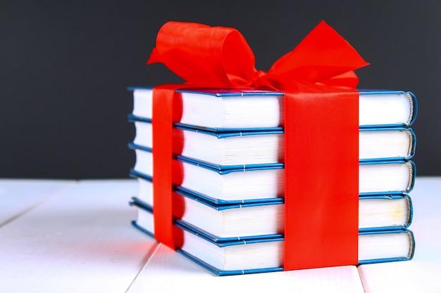 Ein stapel der bücher gebunden mit einem roten band auf einem weißen holztisch. geschenk auf hintergrund einer tafel