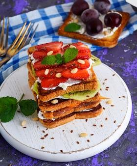 Ein stapel des französischen toasts mit hüttenkäse, erdbeeren, kiwi und blaubeeren