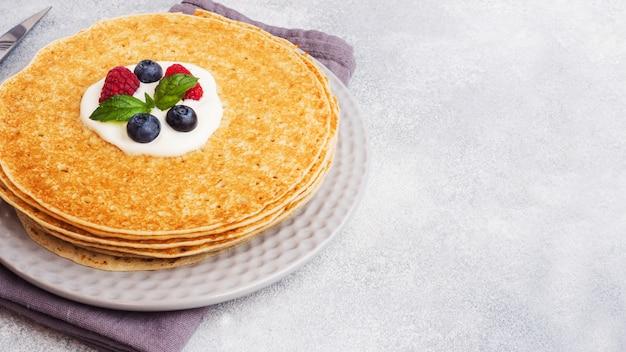 Ein stapel dünner pfannkuchen auf einem weißen teller