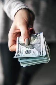 Ein stapel geld, dollar in schönen weiblichen händen. mit einer schönen maniküre. geschäftsvorschlag. moderne mode.