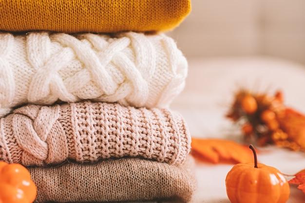 Ein stapel gestrickter pullover in der herbstdekoration aus kürbissen und gelben blättern.