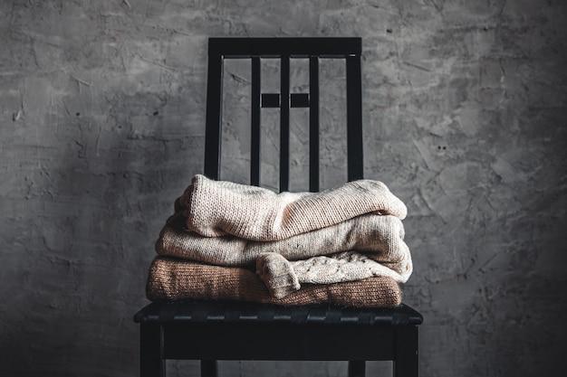 Ein stapel gestrickter, warmer, kuscheliger pullover auf einem stuhl an der grauen wand. herbst, winter konzept.