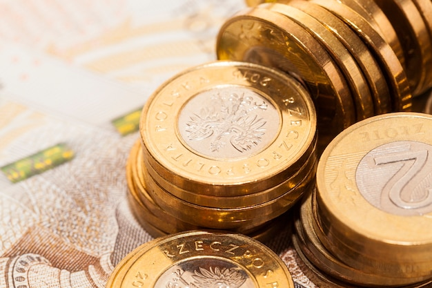 Ein stapel goldfarbener polnischer münzen - zloty, auf neuen polnischen banknoten liegend, nahaufnahmefoto in einem winkel