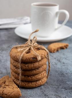 Ein stapel kekse und kaffee in einer weißen tasse. frühstück auf dem tisch. leckeres gebäck. runde hausgemachte kekse.