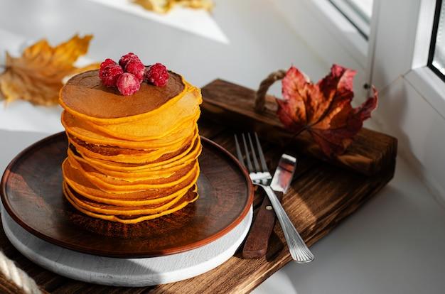 Ein stapel kürbispfannkuchen mit himbeeren.