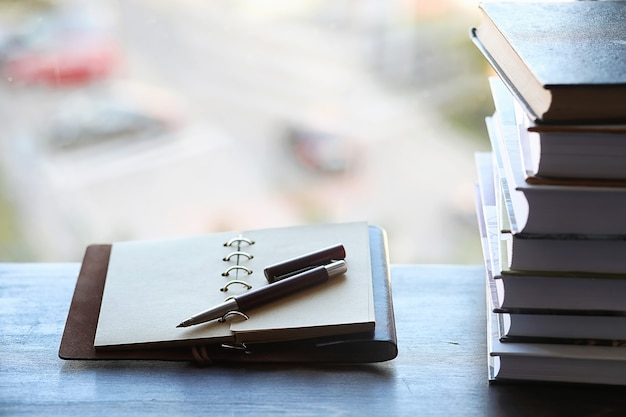 Ein stapel lehrbücher auf der fensterbank und schreibutensilien