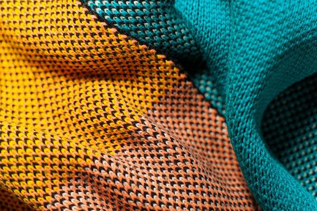 Ein stapel mehrfarbiger synthetischer strickstoffe mit unterschiedlichen strukturen und texturen. ein stapel der bunten stoffe glättet hintergrund. mehrfarbiger strickstoff