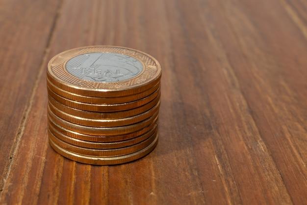 Ein stapel mit vielen echten brasilianischen geldmünzen, die auf einem holztisch gestapelt sind