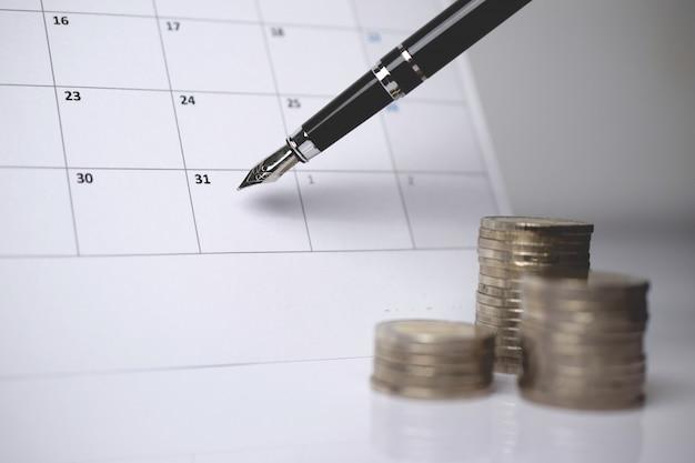 Ein stapel münzen und ein stift auf dem kalender.