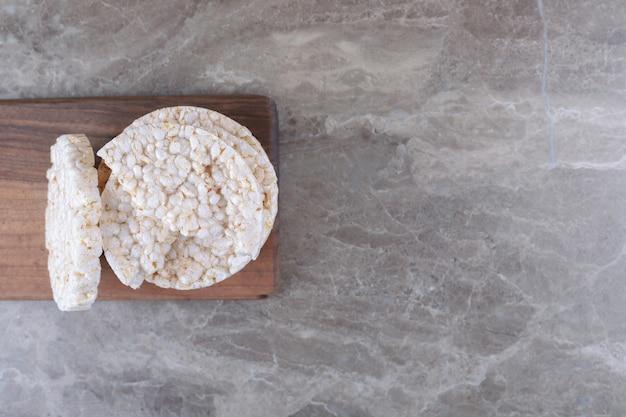 Ein stapel puffreiskuchen auf dem holztablett auf der marmoroberfläche