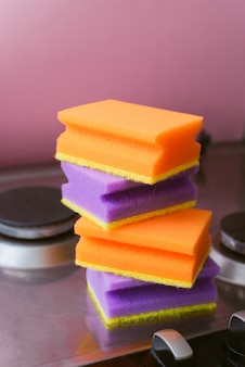 Ein stapel purpurrote und orange schwämme für das waschen auf dem ofen