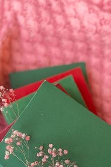 Ein stapel roter und grüner bücher mit trockenen blumen auf einem rosa warmen strickpullover