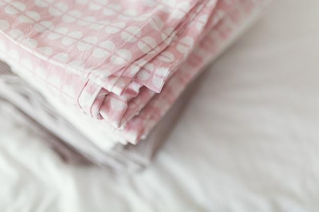 Ein stapel sauberer und gebügelter wäsche liegt auf dem bett