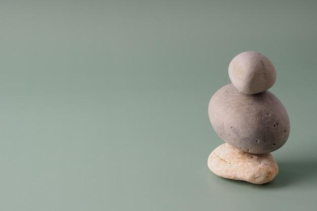 Ein stapel seesteine auf einem pastellfarbenen hintergrund. balance-konzept, kopienraum. spirituelle entspannung, zen. pyramide aus kieselsteinen, harmonie, einfachheit, minimalismus.