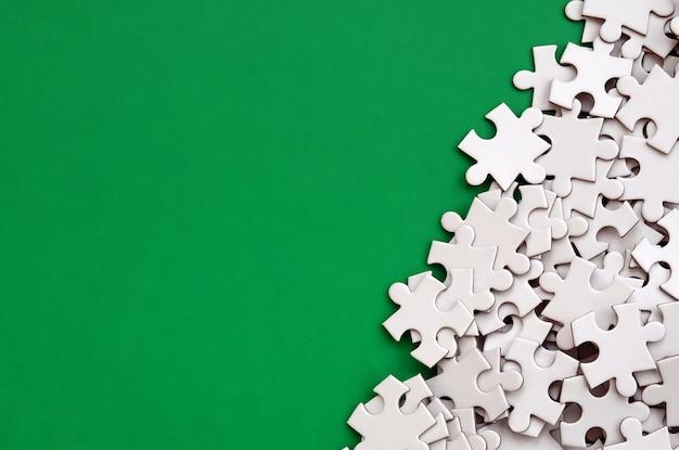 Ein stapel ungekämmter elemente eines weißen puzzles liegt