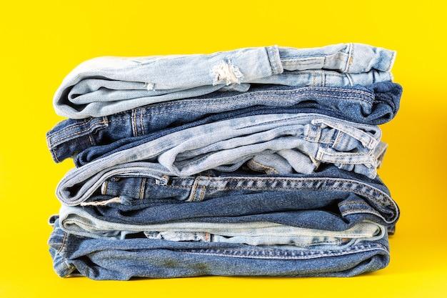 Ein stapel verschiedener jeanshosen hautnah auf gelbem hintergrund, freizeitkleidung