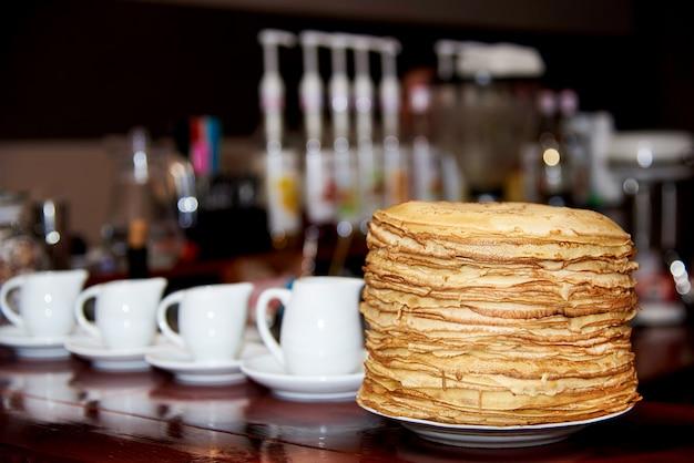 Ein stapel von frischen gekochten pfannkuchen in einer weißen platte steht auf einem holztisch mit geräten