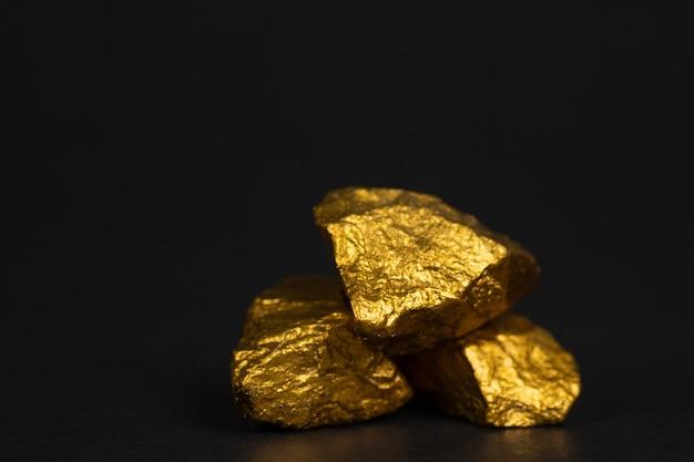 Ein stapel von goldnuggets oder golderz auf schwarzem hintergrund
