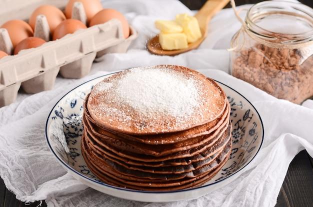 Ein stapel von pfannkuchen mit einem holzlöffel butter, eier, auf einem rustikalen holztisch.