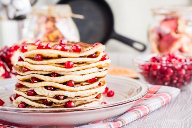 Ein stapel von pfannkuchen mit granatapfelkernen auf einer platte