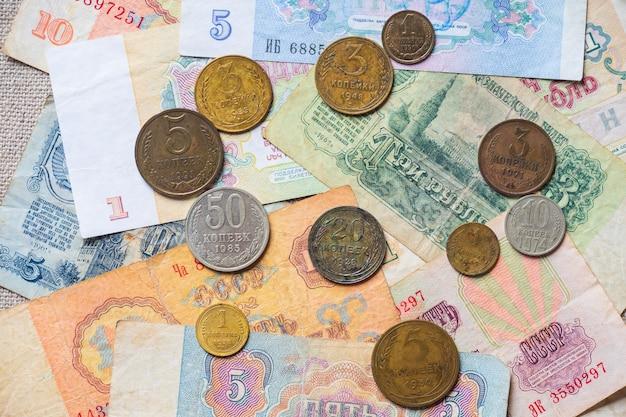 Ein stapel von sowjetischem papiergeld und münzen auf dem tisch zerstreut.