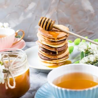 Ein stapel von stückchen nahe bei einer tasse tee und einem glas honig auf einem grauen hintergrund