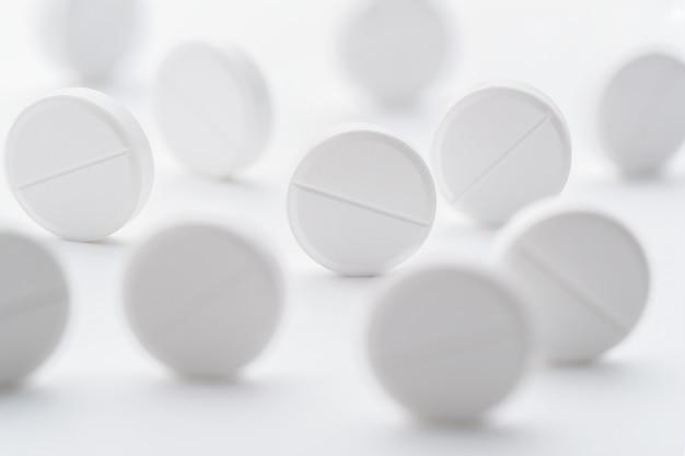 Ein stapel weißer pillen verstreut auf einem hellen weißen hintergrund. selektiver fokus. modelllayout, vorlage.