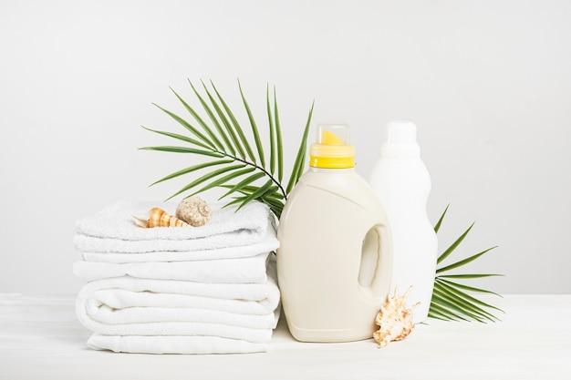 Ein stapel weißes leinen, waschgel und weichspüler auf einem weißen tisch mit muscheln und palmzweigen. mockup-waschtag in einem tropischen hotel. flüssigwaschmittelflasche.