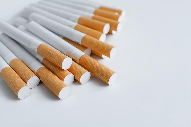Ein stapel zigaretten auf einer weißen tabelle. prävention von schlechten gewohnheiten und sucht. tiefenschärfe.