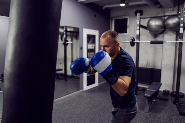 Ein starker treffer im boxsack. ein fokussierter mann trägt boxhandschuhe und sportbekleidung in einem modernen indoor-fitnessstudio mit ausrüstung. ein mann, der boxt, ist gerade dabei, einen riesigen schwarzen boxsack zu treffen
