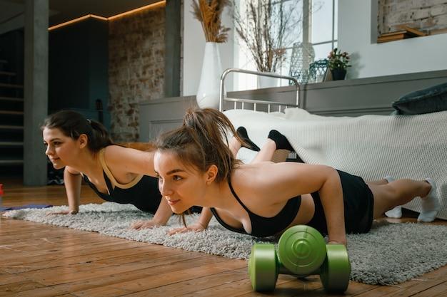 Ein starkes und schönes sport-fitness-mädchen in sportbekleidung, das liegestütze macht