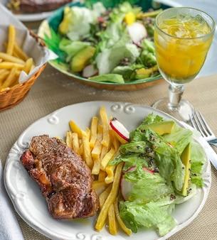 Ein steak, begleitet von einem veganen grünen salat mit avocado, radieschen, salat und quinoa.